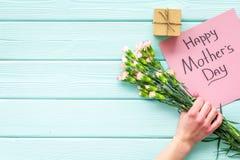 Glückliches Mutter ` s Tageskonzept Handbeschriftung nahe Blumenstrauß der rosa Gartennelke und der Geschenkbox auf dem blauen Tü stockfotografie