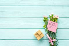 Glückliches Mutter ` s Tageskonzept Handbeschriftung nahe Blumenstrauß der rosa Gartennelke und der Geschenkbox auf dem blauen Tü stockfoto