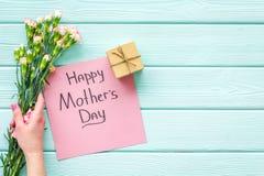 Glückliches Mutter ` s Tageskonzept Handbeschriftung nahe Blumenstrauß der rosa Gartennelke und der Geschenkbox auf dem blauen Tü stockbilder