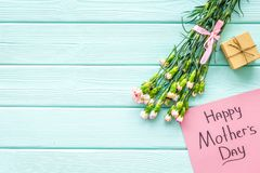 Glückliches Mutter ` s Tageskonzept Handbeschriftung nahe Blumenstrauß der rosa Gartennelke und der Geschenkbox auf dem blauen Tü stockbild