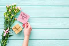 Glückliches Mutter ` s Tageskonzept Handbeschriftung nahe Blumenstrauß der rosa Gartennelke und der Geschenkbox auf dem blauen Tü lizenzfreie stockbilder