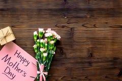 Glückliches Mutter ` s Tageskonzept Handbeschriftung nahe Blumenstrauß der rosa Gartennelke und der Geschenkbox auf die dunkle hö lizenzfreies stockbild
