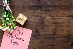 Glückliches Mutter ` s Tageskonzept Handbeschriftung nahe Blumenstrauß der rosa Gartennelke und der Geschenkbox auf die dunkle hö stockfotografie