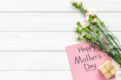 Glückliches Mutter ` s Tageskonzept Handbeschriftung nahe Blumenstrauß der rosa Gartennelke und der Geschenkbox auf die weiße höl lizenzfreies stockfoto
