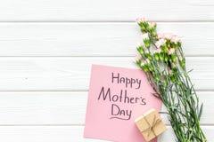 Glückliches Mutter ` s Tageskonzept Handbeschriftung nahe Blumenstrauß der rosa Gartennelke und der Geschenkbox auf die weiße höl lizenzfreie stockbilder