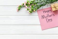 Glückliches Mutter ` s Tageskonzept Handbeschriftung nahe Blumenstrauß der rosa Gartennelke und der Geschenkbox auf die weiße höl stockfoto