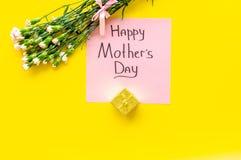 Glückliches Mutter ` s Tageskonzept Handbeschriftung nahe Blumenstrauß der rosa Gartennelke und der Geschenkbox auf Draufsicht de lizenzfreie stockfotografie