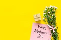 Glückliches Mutter ` s Tageskonzept Handbeschriftung nahe Blumenstrauß der rosa Gartennelke und der Geschenkbox auf Draufsicht de lizenzfreie stockbilder