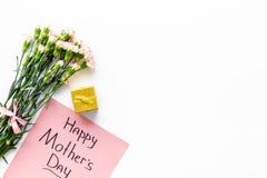 Glückliches Mutter ` s Tageskonzept Handbeschriftung nahe Blumenstrauß der rosa Gartennelke und der Geschenkbox auf weißer Draufs stockfoto