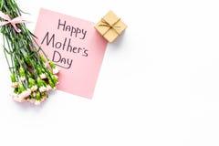 Glückliches Mutter ` s Tageskonzept Handbeschriftung nahe Blumenstrauß der rosa Gartennelke und der Geschenkbox auf weißer Draufs lizenzfreie stockbilder