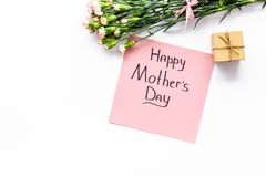 Glückliches Mutter ` s Tageskonzept Handbeschriftung nahe Blumenstrauß der rosa Gartennelke und der Geschenkbox auf weißer Draufs lizenzfreies stockbild