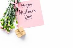 Glückliches Mutter ` s Tageskonzept Handbeschriftung nahe Blumenstrauß der rosa Gartennelke und der Geschenkbox auf weißer Draufs stockfotos