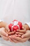 Glädjen av att ge sig - liten gåvaask i kvinna- och barnhänder royaltyfri fotografi