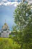 Glänsande guld- kupoler av en rysk ortodox kyrka i Barnaul Royaltyfria Bilder