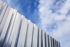Glänsande korrugerat metallstaket och blå molnig himmel Arkivfoton
