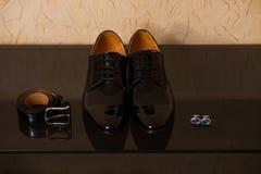 Glänsande läderskor med bältet och cufflinks Arkivfoto