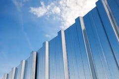 Glänsande metallstaket och blå molnig himmel Arkivfoto