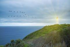 Glänsande skyddande ljus för fyr över havet Royaltyfri Bild