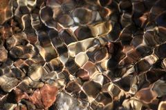 Glänsande textur av färgade stenar i en klar bergliten vik arkivbilder
