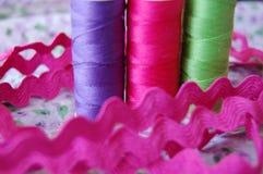 Glänzende bunte Spulen des Fadens in Purpurrotem, im Rosa und in Grünem stockfotografie