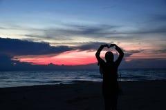 Glänzende Frauen an der Dämmerung am Meernachtbild stockbilder
