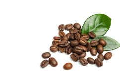 Glänzende frische Röstkaffeebohnen mit den Blättern lokalisiert auf weißem b Stockbild