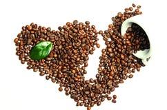 Glänzende frische Röstkaffeebohnen mit der Schale und Blatt lokalisiert auf w Lizenzfreie Stockbilder
