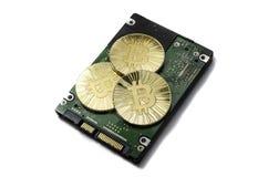 Glänzende Gold-Bitcoin-Münze, die auf Festplattenlaufwerk legt stockfotos