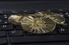 Glänzende Gold-Bitcoin-Münze, die auf schwarze Tastatur legt lizenzfreies stockbild
