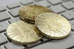 Glänzende Gold-Bitcoin-Münze, die auf weiße Tastatur legt Lizenzfreie Stockbilder