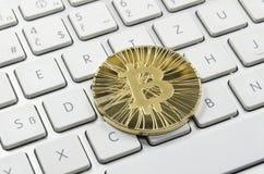 Glänzende Gold-Bitcoin-Münze, die auf weiße Tastatur legt stockfotos