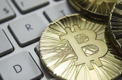 Glänzende Gold-Bitcoin-Münze, die auf weiße Tastatur legt Stockbild
