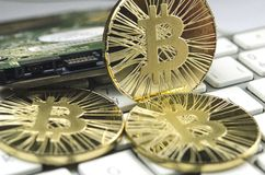 Glänzende Gold-Bitcoin-Münze, die auf weiße Tastatur legt Lizenzfreie Stockfotografie