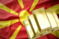 Glänzende goldene Goldbarren auf der Macedonia-Flagge Stockfotos