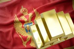 Glänzende goldene Goldbarren auf der Montenegro-Flagge Stockbild