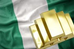 Glänzende goldene Goldbarren auf der Nigeria-Flagge Lizenzfreie Stockfotografie