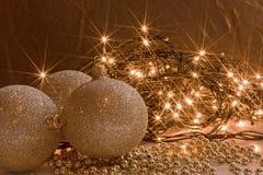Glänzende goldene Verzierungen und Weihnachtsleuchten garl Stockfotografie