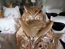 Glänzende keramische Figürchen-Eule versiegelt Stellung nacheinander in Folge auf den Regalen stockfoto