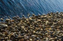 Glänzende Kieselsteine durch das Meer lizenzfreie stockfotos