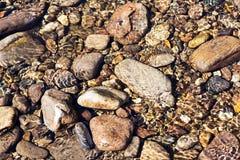Glänzende Kräuselungen des transparenten klaren Wassers auf dem Flusskiesel stockbild