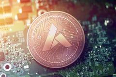 Glänzende kupferne BEGEISTERUNG cryptocurrency Münze auf undeutlichem Motherboardhintergrund stockfotos