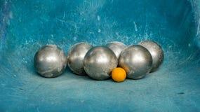 Glänzende Metall-Petanque-Bälle und orange hölzerner Ball auf blauer Knickente stockbilder