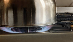 Glänzende Metallküchen-Warenkosten auf dem beleuchteten Gas setzen sich in Brand Lizenzfreie Stockfotografie