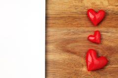 Glänzende rote Herzen auf hölzernem Hintergrund Stockbilder