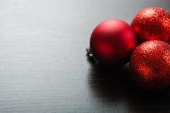 Glänzende rote Weihnachtsbälle auf schwarzem hölzernem Hintergrund Stockfotografie
