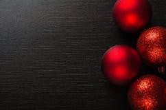 Glänzende rote Weihnachtsbälle auf schwarzem hölzernem Hintergrund Lizenzfreie Stockfotografie