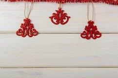 Glänzende rote Weihnachtsverzierungen auf weißem hölzernem Hintergrund Stockfoto