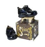 Glänzende schwarze Schuhe auf einem Schuh-Glanz-Kasten Stockbild