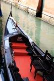 Glänzende schwarze und rote Gondel im venetianischen Kanal Stockbild