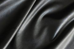 Glänzende, seidige und glatte Oberfläche des schwarzen Gewebes stockbilder